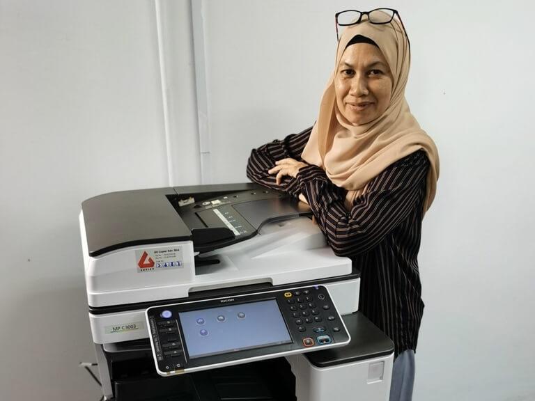 Happy Customer in Bandar Tun Hussien Onn posing beside a Ricoh Photocopier