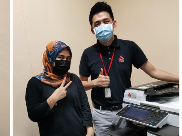 Satisfied customer posing beside a rented Ricoh MPC3503 in Kuala Lumpur